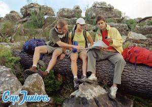 3 ados lisent une carte en course d'orientation lors d'une randonnée montagne