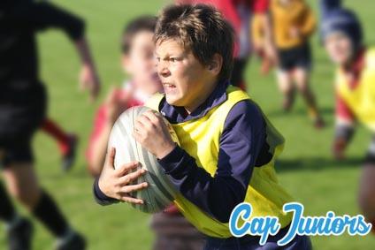 Un jeune garçon en plein effort pour aller marquer un essai lors d'un stage sportif de rugby