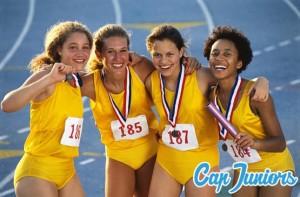 4 jeunes filles athlètes posent devant l'appareil photo après leurs courses